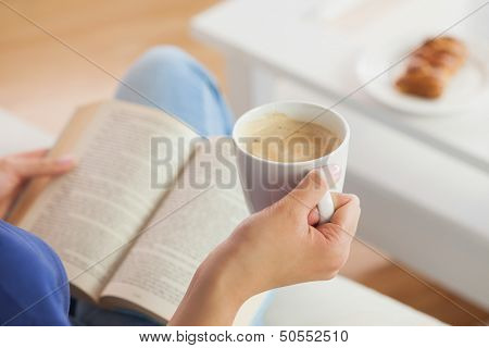 Woman sitting on the sofa reading a book holding her coffee mug in living room at home