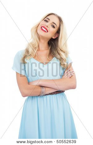 Content blonde model in blue dress posing crossed arms on white background