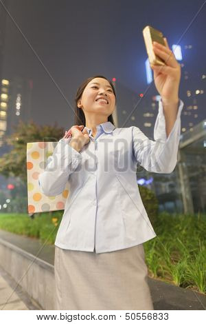 Young businesswoman taking a picture of her self with her cell phone