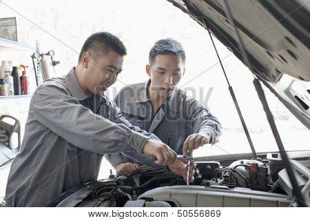 Two Garage Mechanics Working on Engine
