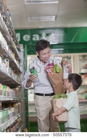 Father and son shopping together in supermarket, Beijing