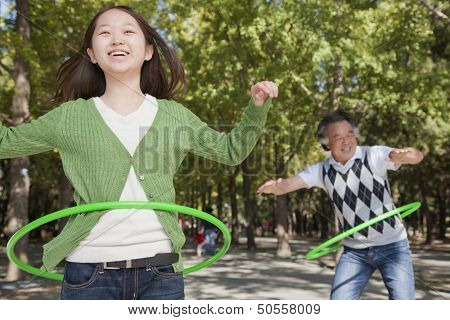Granddaughter with grandfather playing with plastic hoop in the park