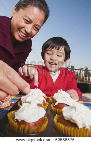 Grandmother and grandson decorating cupcakes