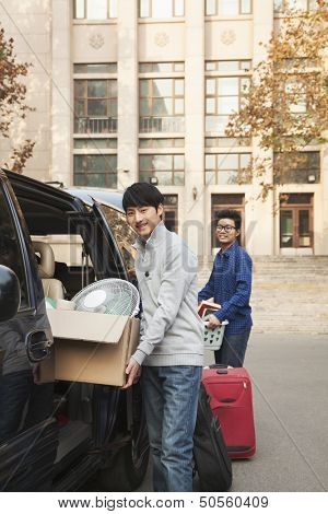 Students moving into dormitory on college campus