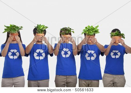 Group of people holding plants, obscuring faces, studio shot