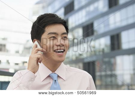 Young Businessman in pink button down shirt on the phone, Beijing, China