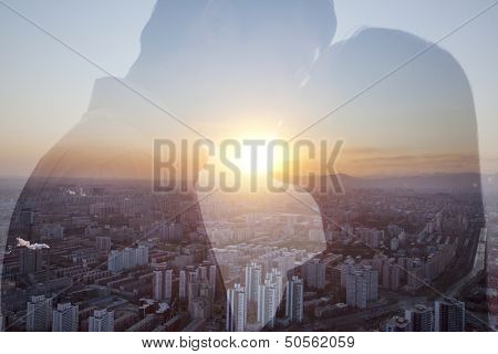 Double exposure of couple kissing over cityscape