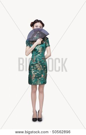 Young Woman with Qipao Covering Her Face with Fan