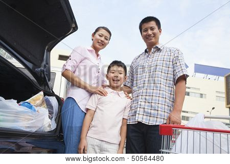 Family standing next to the car with shopping bags