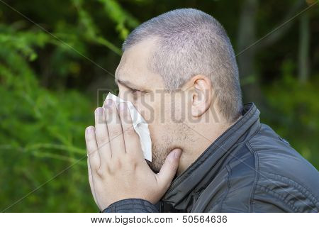 Man with a runny nose and napkin