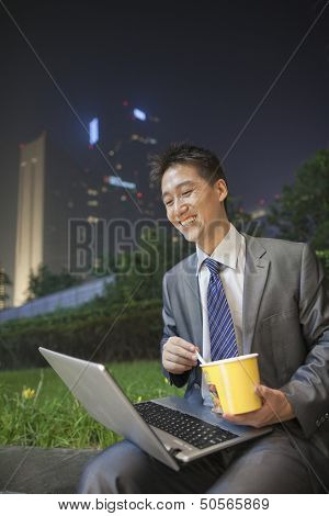 Young businessman working outdoors and eating