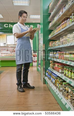 Sales clerk checking merchandise in supermarket