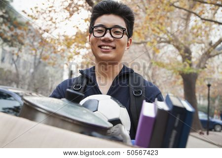 Student in front of dormitory at college