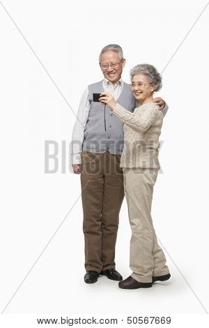Senior couple taking picture with digital camera