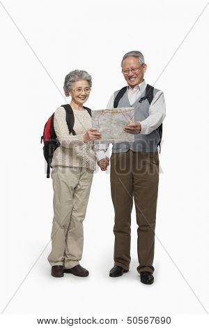Senior couple with backpacks checking map