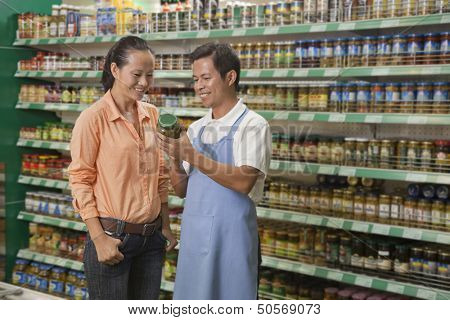 Sales clerk assisting women, examining jar in the supermarket, Beijing
