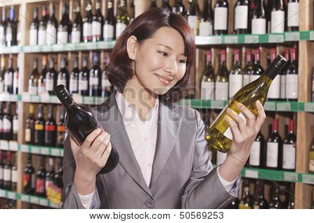 Mid Adult Woman Choosing Wine in a Liquor Store