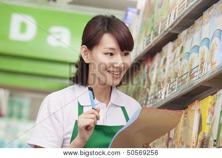 Sales Clerk Checking Groceries in Supermarket