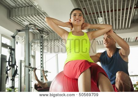 Young women exercising with her personal trainer in the gym