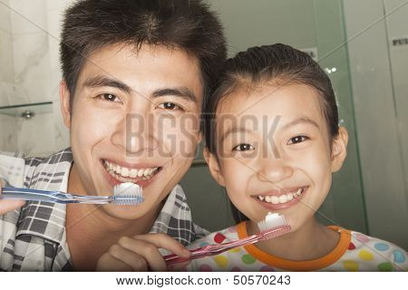Father and Daughter Brushing Teeth Together