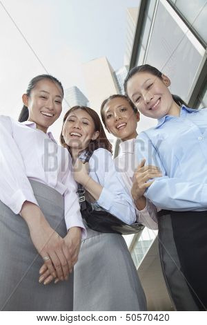 Four young businesswomen looking at the camera