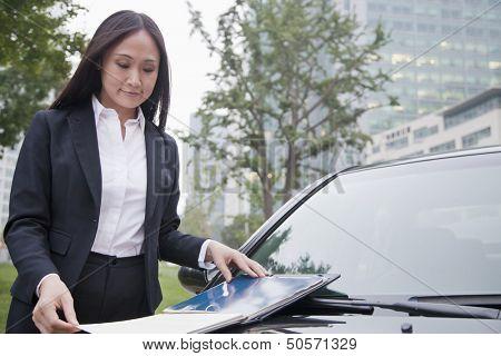 Mature Businesswoman Looking Down Notebook