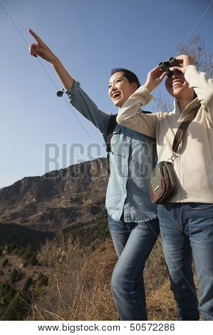 Women hiking, using binoculars, pointing at the mountain top