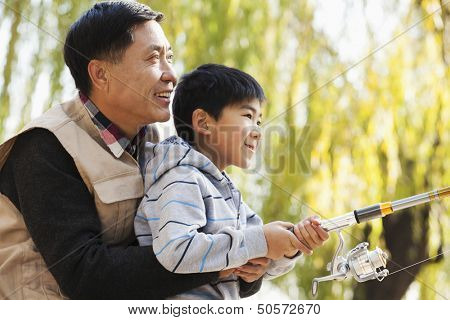 Father and son fishing together at lake