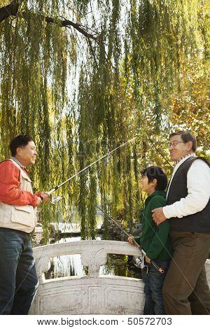 Multi-generational men fishing at lake