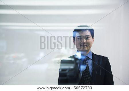 Businessman looking thorough window in parking garage