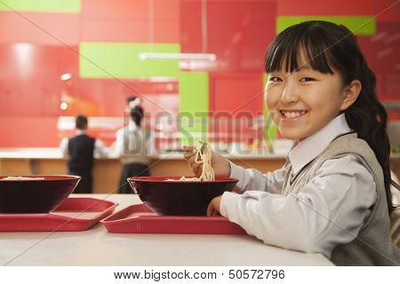 School girl eats noodles in school cafeteria