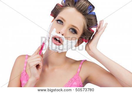Model in hair curlers shaving her face and looking at camera on white background