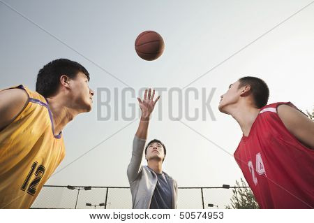 Referee throwing ball in the air, basketball players getting ready for a jump