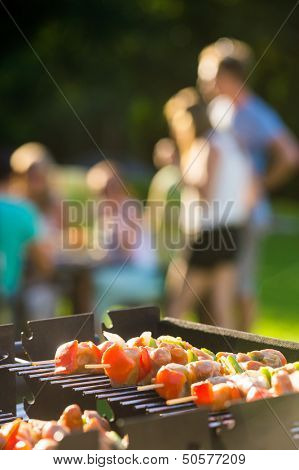 Close-up of skewers grilling on barbecue at garden party