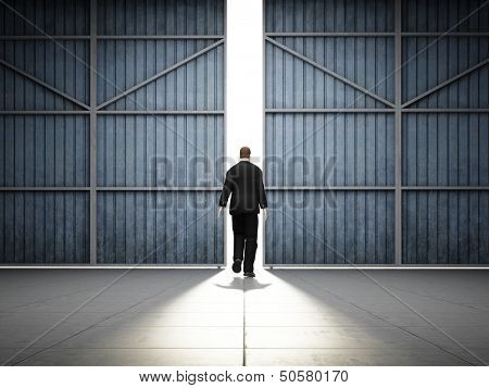Man walks into light of large hangar doors