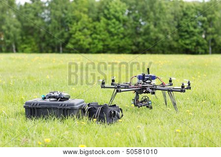 UAV helicopter with toolbox and bag in park