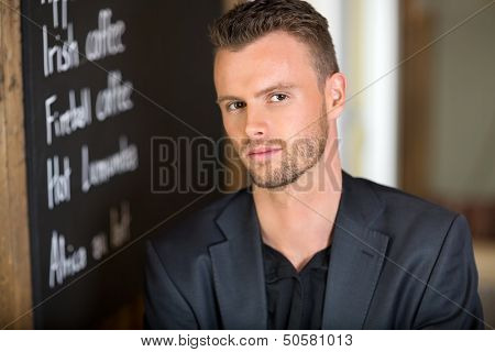 Portrait of confident businessman next to chalkboard at coffeeshop