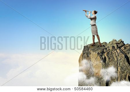 Image of businesswoman looking in telescope standing atop of rock