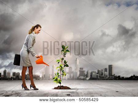 Image of businesswoman watering tree with pot. Ecology concept