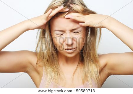 young blond woman with a headache holding head