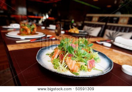 Appetizer with rare fried tuna and salmon on restaurant table