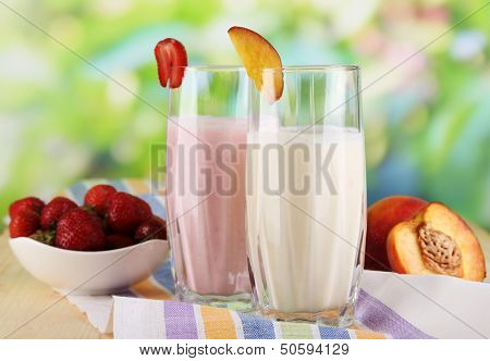 Delicious milk shakes with strawberries and peach on wooden table on natural background