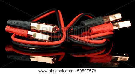 Car battery jumper cables on black background