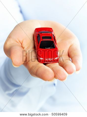 Hand with a red car. Dealership concept .