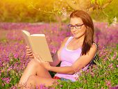Attractive student girl sitting on pink floral field and read book, doing homework outdoors, wearing