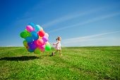 stock photo of meadows  - Happy little girl holding colorful balloons - JPG