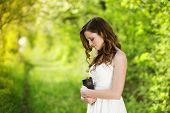 stock photo of scriptures  - Beautiful woman with Bible is in sunny nature - JPG
