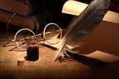 foto of inkpot  - Vintage still life with inkpot and pen near scroll on wooden table - JPG