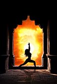 stock photo of virabhadrasana  - Yoga virabhadrasana I warrior pose by woman silhouette in old temple arch at dramatic sunset sky background - JPG