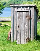 pic of outhouses  - an old wooden outhouse by the river in the country - JPG